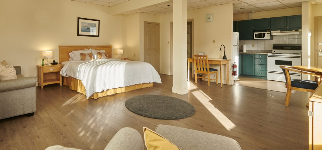 View of the King sized bed form a lounge chair in room 201