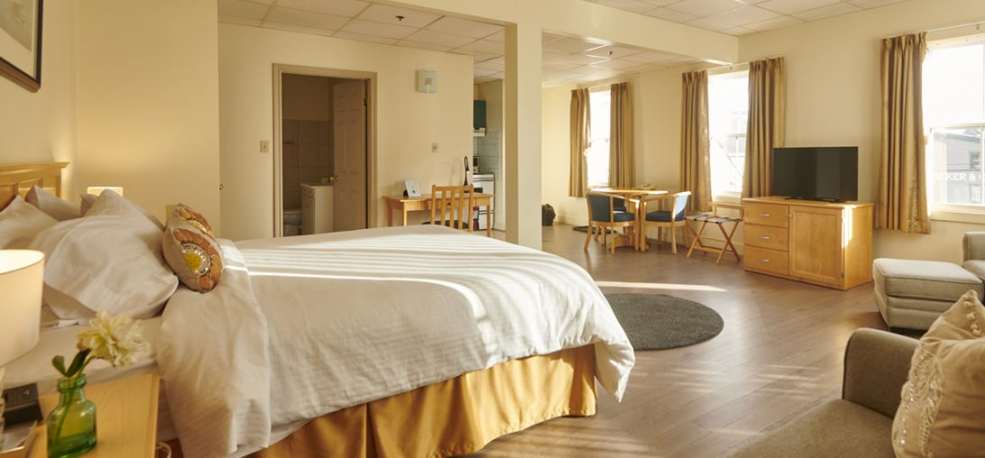 King sized bed with yellow sheets in room 201