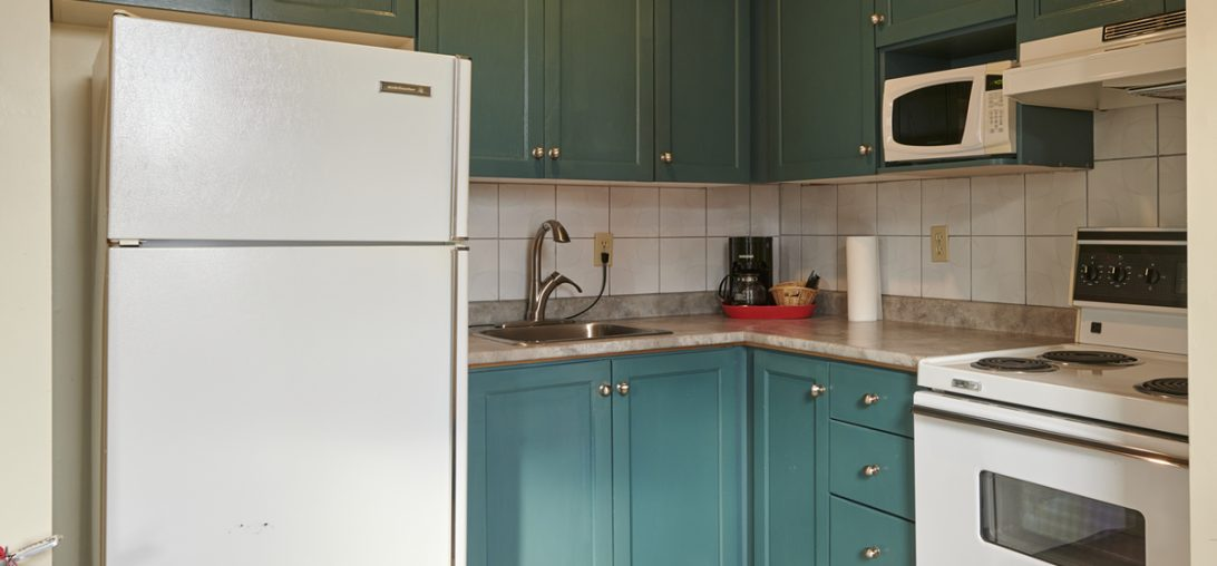 Kitchen with blue cabinets in room 201