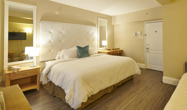 King Sized bed with two side tables and large mirrors in Room 206
