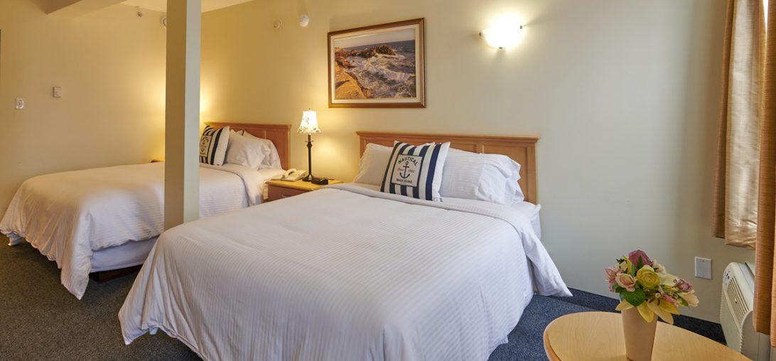 Dual Queen beds with elegant wooden headboards