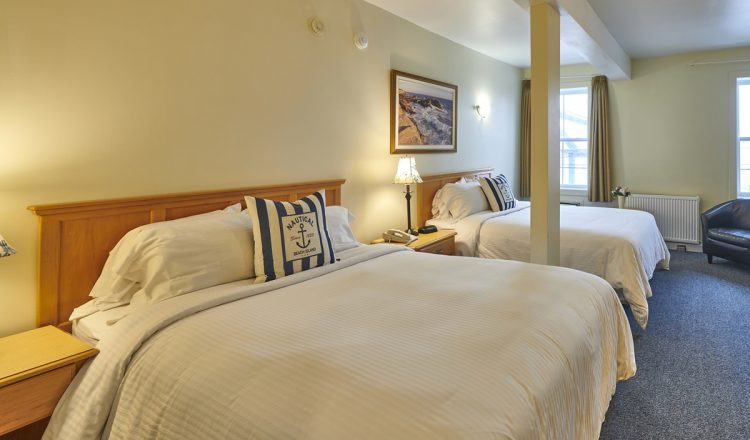Two Queen sized beds with blue and white nautical themed pillows in Room 211