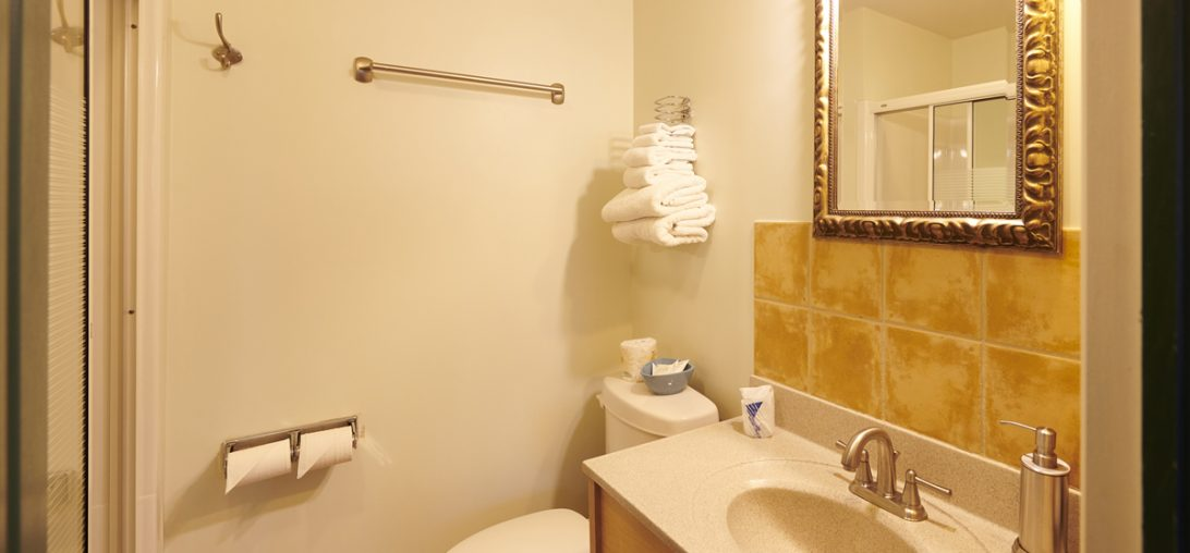 Bathroom with elegant yellow wall tiles and a white sink in Room 211