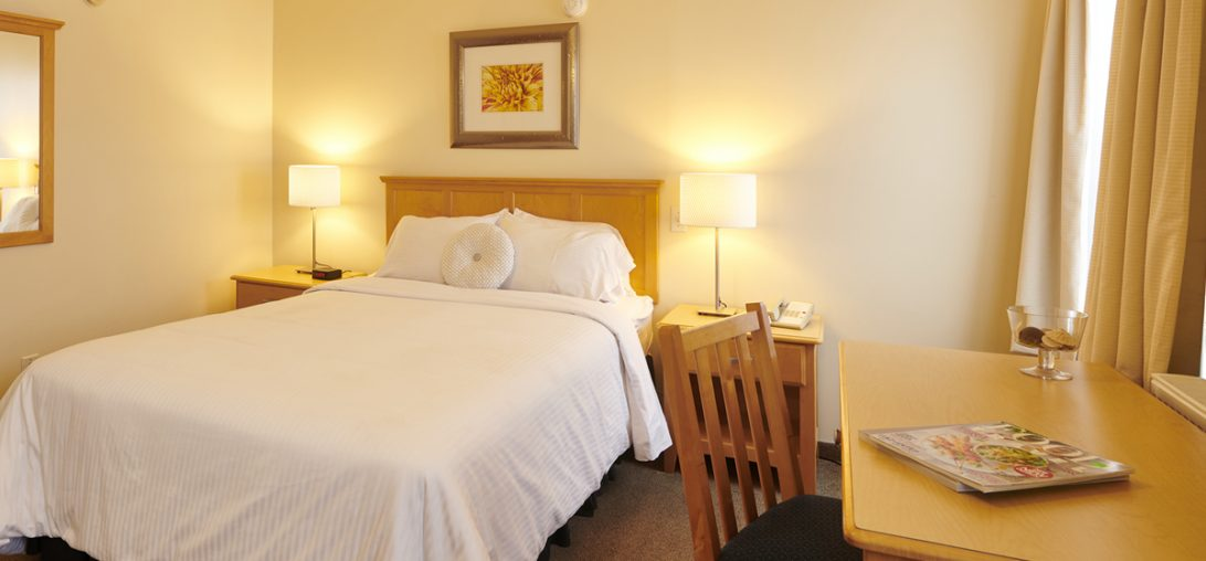 A queen sized bed featuring an elegant wood back board and round pillows in Room 308