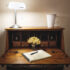 a beautiful wooden writing desk with a lamp and flowers at the Smuggler's Cove Inn.