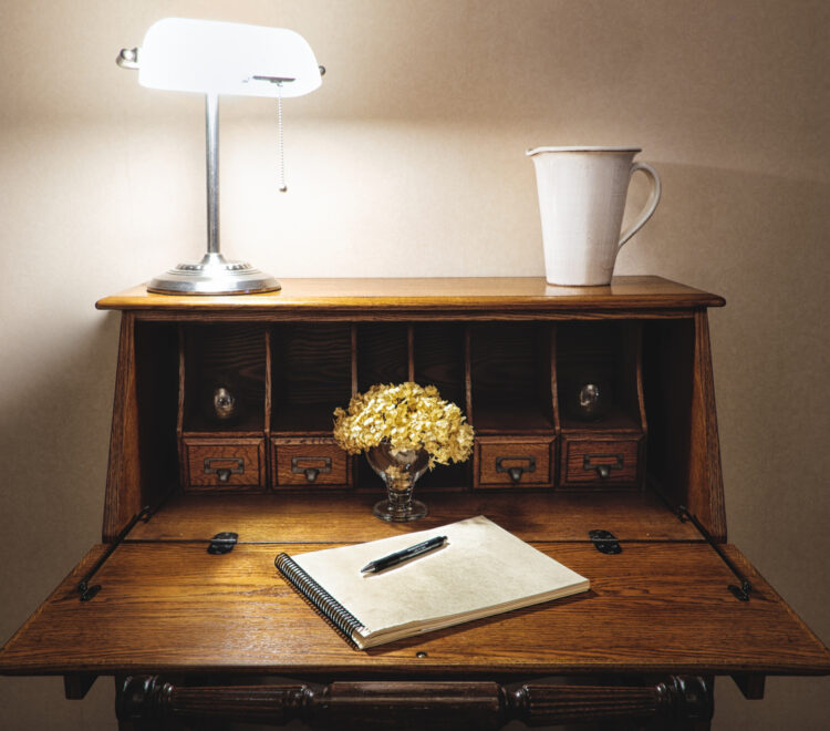 a beautiful wooden writing desk with a lamp and flowers