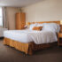 a king sized bed with a golden coloured pillow and a large wardrobe at the Smuggler's Cove Inn.
