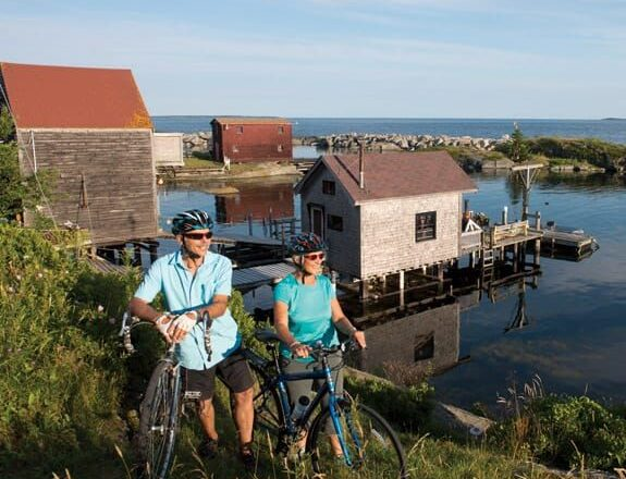 a couple in blue cycling the hills of Lunenburg, NS.