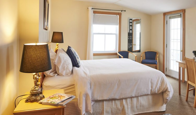 King sized bed set against the back cream coloured wall with a large window in Room 302