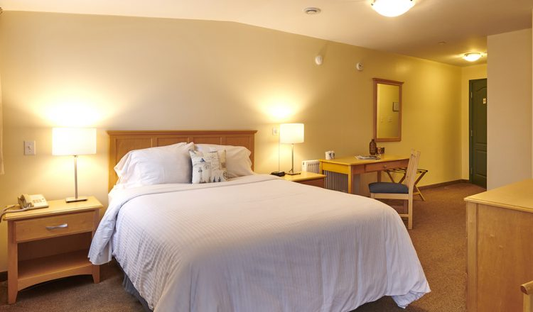 Queen sized bed and two side tables with lamps and a wooden back board in room 303.