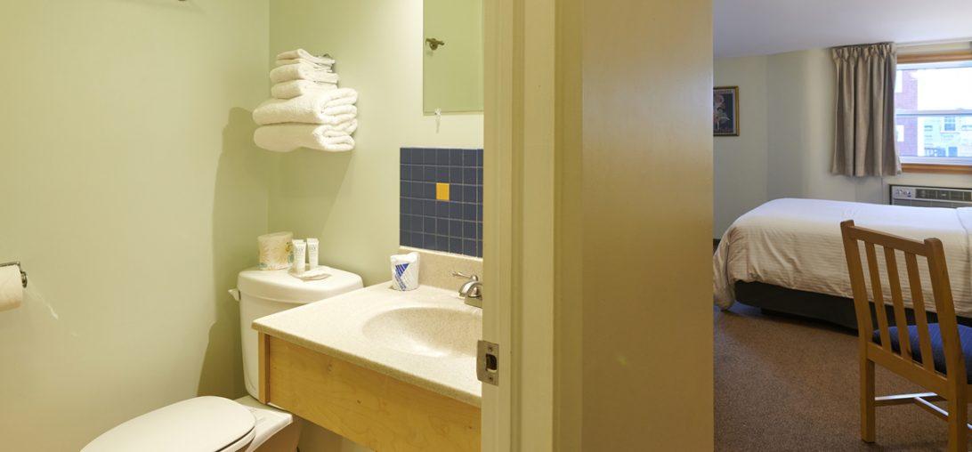 door way showing bathroom and bed in room 303.