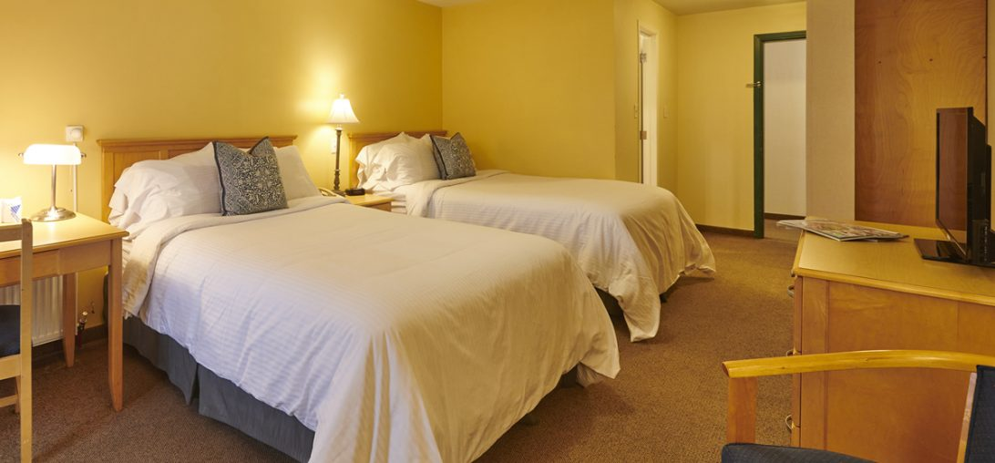 Double beds with two side tables and wooden back boards in room 304.