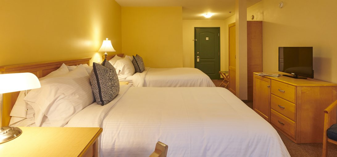two Double beds with pillows with intricate blue designs in room 304.