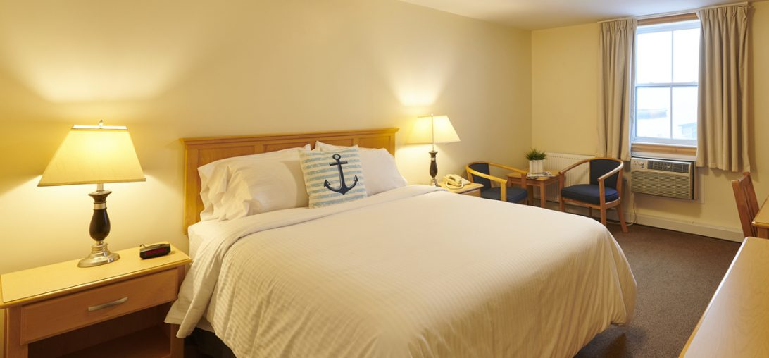 a Queen sized bed with a blue and white anchor pillow in room 311