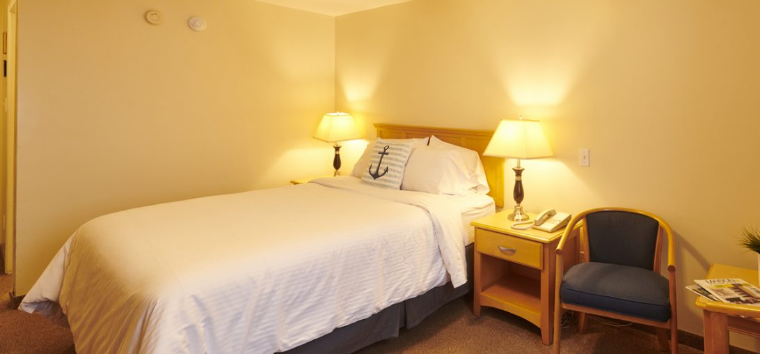 bed with two side tables and a anchor pillow in Room 311