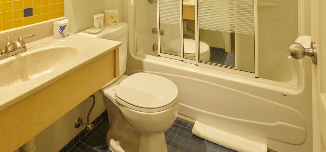 Interior of bathroom with blue tiled floors and yellow tiled walls in Room 311.