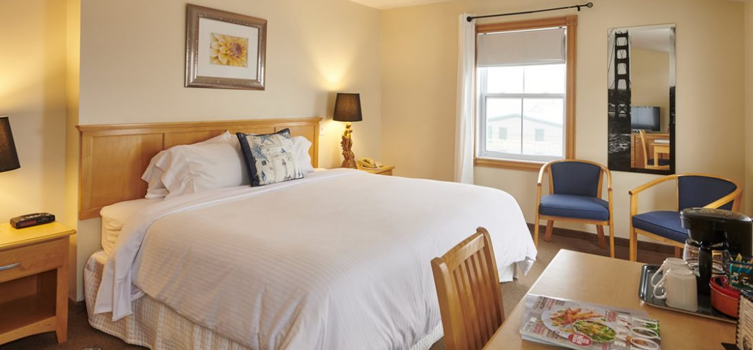 a king sized bed with white sheets and an artistic pillow.