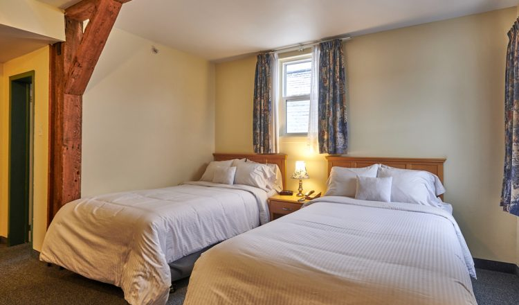 Two Double beds with an intricate wall trim in room 207