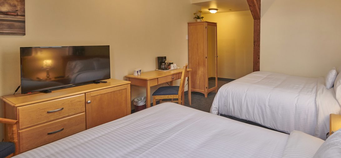 Two Double Beds with a large flat screen in room 207.