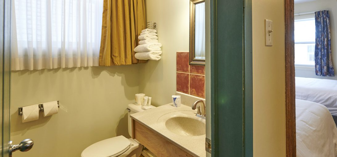 Bathroom with a white counter and red tile walls in room 207.