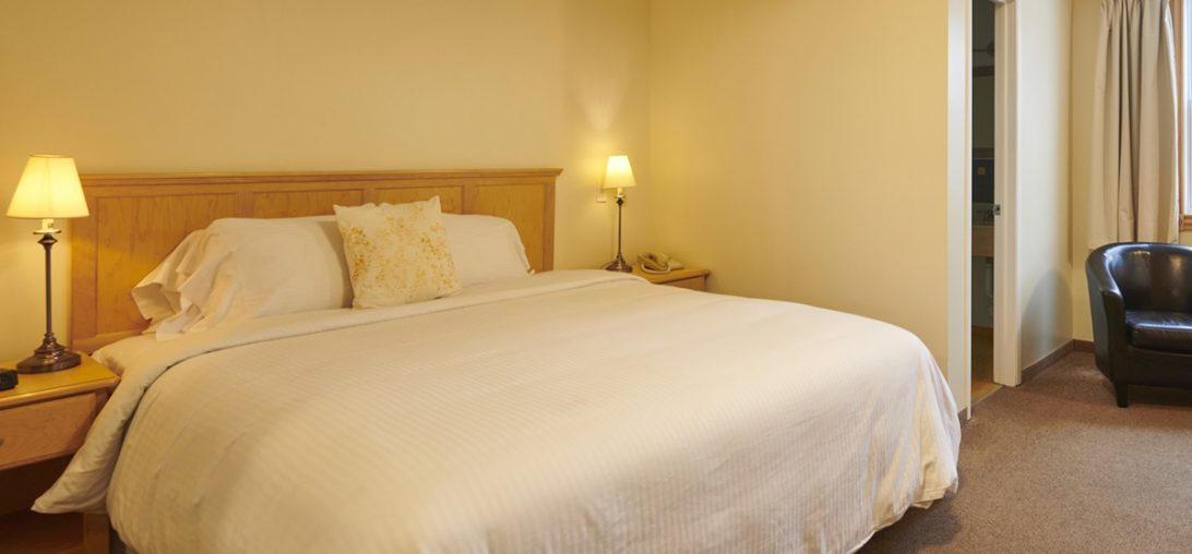 King sized bed with white comforter and wooden head board in room 306.