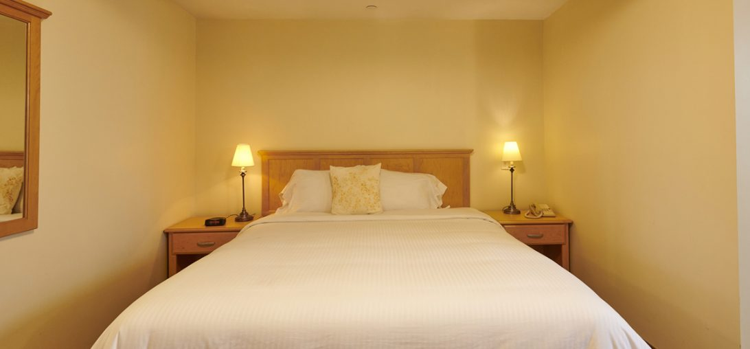 a front view of a King Sized bed with two side tables in room 306
